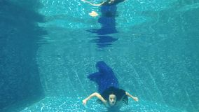 Charming brunette in long dress swims underwater. Underwater. Beautiful brunette in long blue dress dives under water in swimming pool. Charming girl poses for stock footage