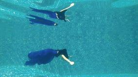 Charming brunette in luxury dress swims under water. Underwater. Beautiful brunette in long blue dress dives under water in swimming pool. Charming girl poses stock video