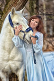 Charming brunette in pale blue dress with a white horse Royalty Free Stock Photography