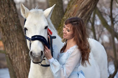 Charming brunette in pale blue dress with a white horse Royalty Free Stock Images