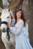 Charming brunette in pale blue dress with a white horse Royalty Free Stock Photos