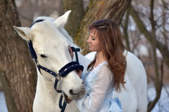 Charming brunette in pale blue dress with a white horse Royalty Free Stock Photo