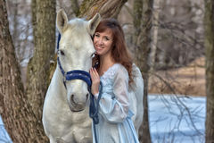 Charming brunette in pale blue dress with a white horse Stock Photography