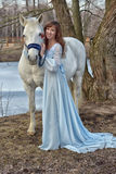 Charming brunette in pale blue dress with a white horse Stock Image
