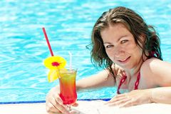 Charming brunette in the pool holding a glass of alcoholic cocktail Royalty Free Stock Photography
