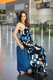 Charming brunette posing in airport. Sitting on a suitcase dressed in a long dress stock photos
