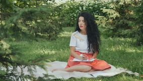Charming brunette relaxing on plaid in park and writes poems stock video footage