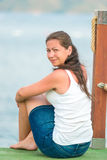 Charming brunette resting sitting on a pier Stock Image