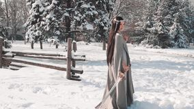 Charming brunette stands alone at the exit from her village, lowers her sword in snow and looks sad down, militant