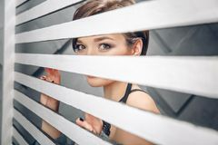 Charming brunette woman looking throughout closed window shutters in half-light. Mysterious atmosphere. Charming brunette woman looking throughout closed window royalty free stock photography