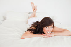 Charming brunette woman posing while lying Stock Photos