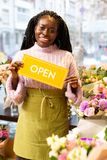 Charming brunette worker demonstrating yellow card for visitors. Look at me. Amazing shop assistant expressing positivity while working in flowershop royalty free stock image