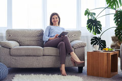 Charming brunette working in laptop while sitting on sofa Royalty Free Stock Photo