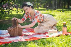 A charming brunette young girl enjoys a rest and a picnic on the green summer grass alone. pretty woman have a holiday and spend v. Acantions on the nature stock photos
