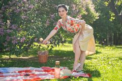 A charming brunette young girl enjoys a rest and a picnic on the green summer grass alone. pretty woman have a holiday and spend v. Acantions on the nature stock photography