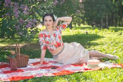 A charming brunette young girl enjoys a rest and a picnic on the green summer grass alone. pretty woman have a holiday and spend v. Acantions on the nature royalty free stock photography