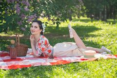 A charming brunette young girl enjoys a rest and a picnic on the green summer grass alone. pretty woman have a holiday and spend v. Acantions on the nature stock images
