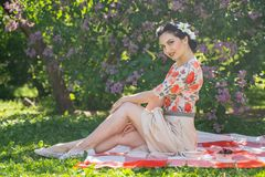 A charming brunette young girl enjoys a rest and a picnic on the green summer grass alone. pretty woman have a holiday and spend v. Acantions on the nature stock photo