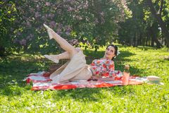 A charming brunette young girl enjoys a rest and a picnic on the green summer grass alone. pretty woman have a holiday and spend v. Acantions on the nature stock image