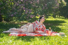 A charming brunette young girl enjoys a rest and a picnic on the green summer grass alone. pretty woman have a holiday and spend v. Acantions on the nature royalty free stock image