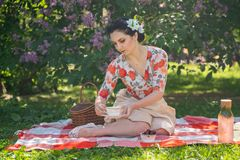 A charming brunette young girl enjoys a rest and a picnic on the green summer grass alone. pretty woman have a holiday and spend v. Acantions on the nature royalty free stock photos