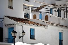 Charming buildings and blue doors and windows in Frigiliana - Spanish white village Andalusia. Beautiful and charming with its narrow streets and footpaths white Stock Photo