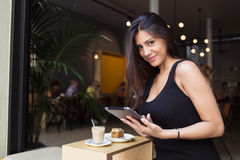 Charming business latin woman holding digital tablet while sitting in modern coffee shop during breakfast in summer day Royalty Free Stock Image