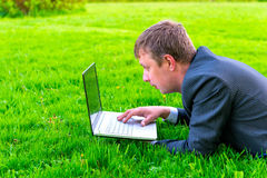 Charming businessman lies on the grass Royalty Free Stock Images
