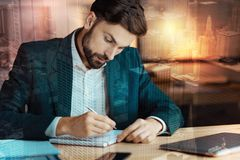 Charming businessman writing in his daily planner. Thorough planning. Handsome bristled young businessman in a suit sitting at the table and writing in his daily Stock Photos