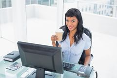 Charming businesswoman holding a cup of coffee Stock Photos