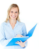 Charming businesswoman holding a folder smiling. At camera against white background Royalty Free Stock Photo