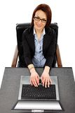 Charming businesswoman with laptop in front, looking up Royalty Free Stock Photo