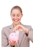 Charming businesswoman saving money in a piggybank. Isolated on a white background Stock Photo