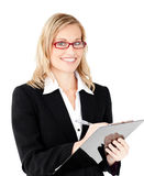 Charming businesswoman writing on a clipboard. Against white background Royalty Free Stock Photos