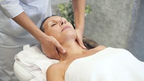 Woman enjoying neck massage in resort spa center stock video
