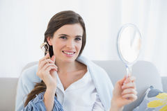 Charming casual brown haired woman in white pajamas holding an eyelash curler Stock Images