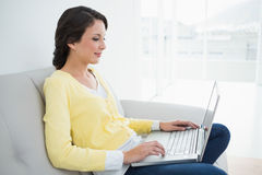 Charming casual brunette in yellow cardigan typing on a laptop Stock Images
