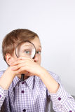 Charming blond caucasian boy in purple shirt looking through a magnifying glass in amazement Royalty Free Stock Photos