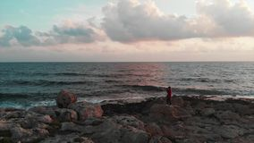 Charming caucasian girl standing on big stone at rocky seashore and taking photos of beautiful mediterranean sea at sunset. Drone. Aerial shot stock footage