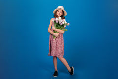 Charming cheerful little girl standing and holding bouquet of flowers Stock Image