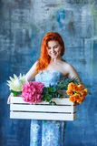 Charming cheerful red hair female shop assistant holds wooden box with flowers with Hydrangea purple, freesia, protea, roses. Flower shop and floristic design royalty free stock images