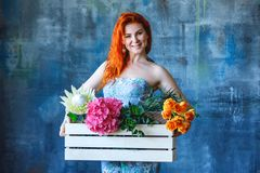 Charming cheerful red hair female shop assistant holds wooden box with flowers with Hydrangea purple, freesia, protea, roses. Flower shop and floristic design stock photography