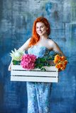Charming cheerful red hair female shop assistant holds wooden box with flowers with Hydrangea purple, freesia, protea, roses. Flower shop and floristic design royalty free stock photography
