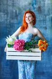 Charming cheerful red hair female shop assistant holds wooden box with flowers with Hydrangea purple, freesia, protea, roses. Flower shop and floristic design royalty free stock photo