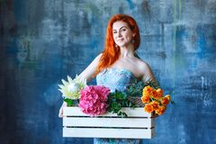 Charming cheerful red hair female shop assistant holds wooden box with flowers with Hydrangea purple, freesia, protea, roses. Flower shop and floristic design stock image