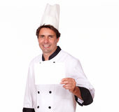 Charming chef holding a blank card of copyspace Stock Photos