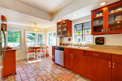 Charming cherry wood kitchen with tile floor. Stock Photo