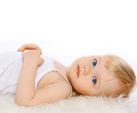 Charming child girl blonde hair on a white background. Closeup portrait calm baby Royalty Free Stock Photos