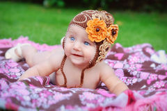 Charming child. Little girl with hat lying on her stomach Stock Photography