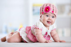 Charming child little girl with hat lying on her stomach Royalty Free Stock Images